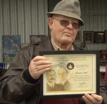 Reece shows off his Wright Brothers Memorial award. He received the award for 50 years of flying.