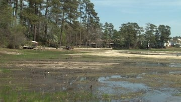 Water is replaced with dirt on Cary Lake due to a failed privately owned dam.