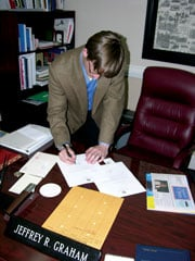 Performing his mayoral duties in his small City Hall office, Jeffrey Graham signs a letter from the city.