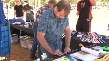 Kevin Peterson works on PVC broomsticks to sell to fans during the US Quidditch Cup.