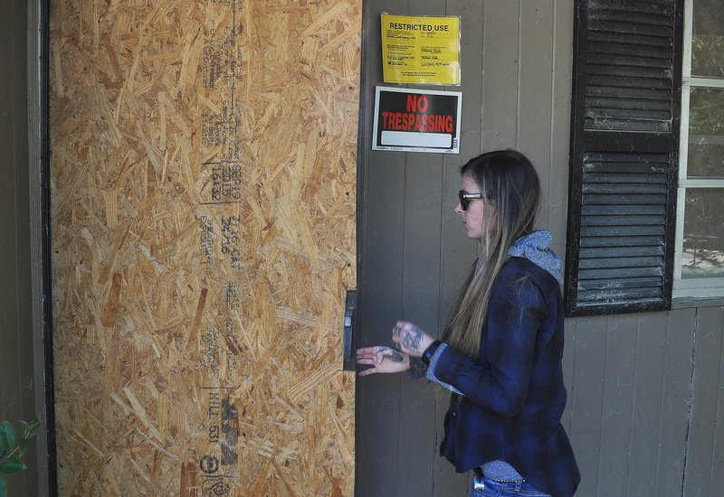 Rachel Larratt, a resident of Gills Creek, enters one of the many homes destroyed by the flood. Although most houses are now stripped and boarded up, some of doors remain open – this door locks by putting a cinderblock in front of it.