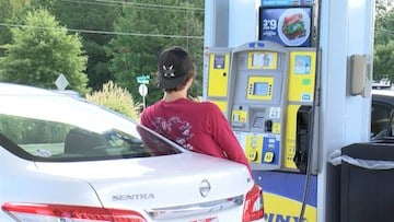 A customer fills up his car at a gas station that isn't experiencing a shortage.