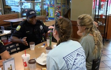 Columbia police officer has breakfast with two USC students before they go to class.