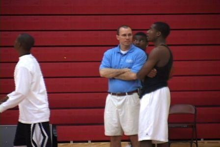 A. C. Flora Basketball Coach Austin Coleman standing with one of the players.