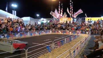 Fair goers line up hours before the race starts to make sure they get a good seat.