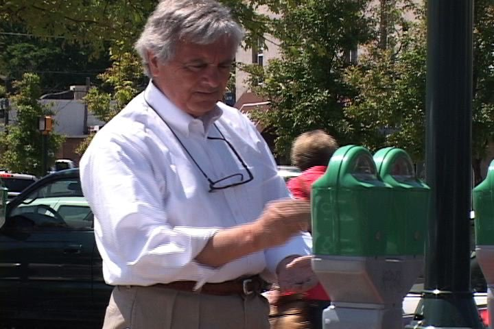 Randy Dennis fills customer's meters in front of his store
