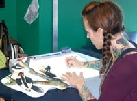 Body Rites Tattoo employee Shannon Pervis works on a drawing of a tattoo that she will soon put on a customer.  Pervis says good tattooing is a work of art and it is not  immoral.