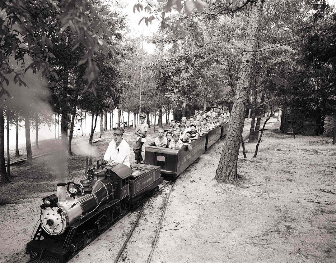 Children catch a ride on the steam propelled train that rounded the park. In this 1967 photograph, Joe Childers mans the engine car.