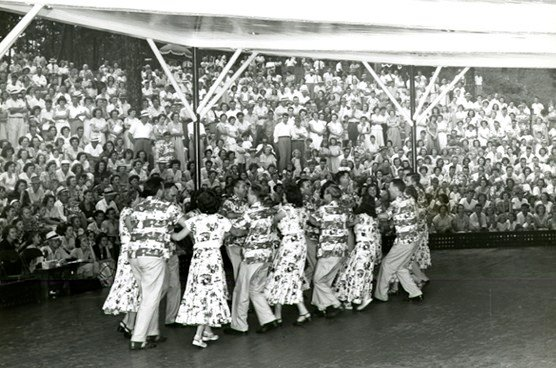 Springs parks goers wearing Springmaid shirts and dresses during a square dancing demonstration. This photograph was taken circa 1950.