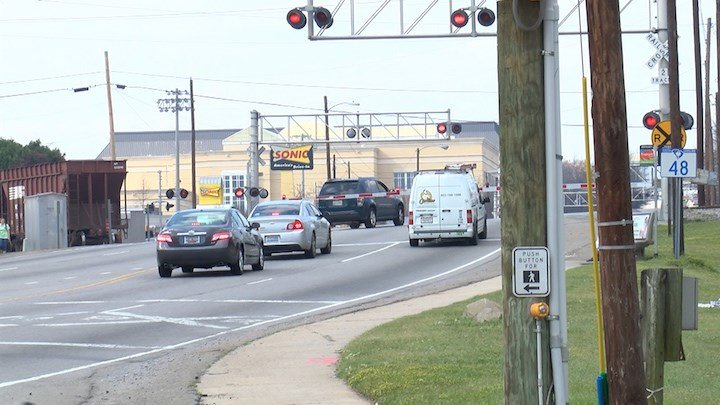 Drivers and pedestrians often make unsafe choices when trains are stopped or not actually on the road. This driver is going through the lowered barriers with a stopped train nearby.