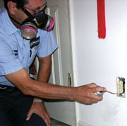 Jimmy Simms of Modern Exterminating treats an electrical socket for bedbugs, which can nest anywhere within 15 feet of their human host.