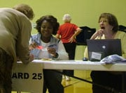 Poll manager Kay Durham and Britne Johnson process voters Ward 25 at the Kilbourne Baptist church precinct.