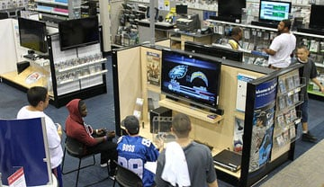 Best Buy customers try out what they want for Christmas while shopping on Black Friday.