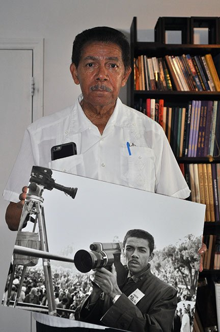 Cecil Williams holding an enlarged print of himself in his younger years. Williams is a renowned photojournalist and has worked in the same studio for 25 years in Orangeburg.