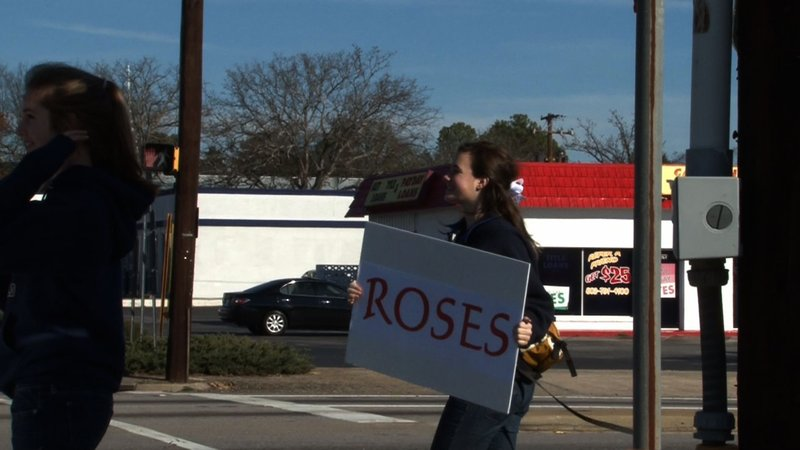Youth Corp Members advertising their roadside rose stand to cars passing by.