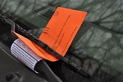 A parking ticket rests under the windshield wiper of an illegally parked car on Devine Street.