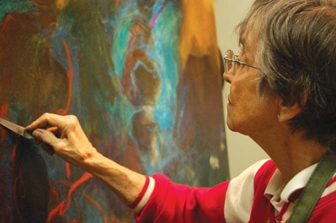 """Laura Spong uses a palette knife to touch up """"We All Live Downstream,"""" a piece from her Feb. 11-22 exhibit at Gallery 80808. Spong is working abstract expressionism and she is finally getting recognition for it, at age 85."""