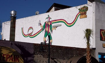 McClellan Douglas' mural of a jester on The Village Idiot pub, which he painted in 2004, looks down toward Saluda Street in Five Points.