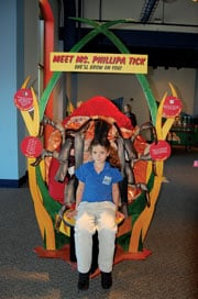 "Madison Meece, a second grader at Oakwood Christian School, sits on the giant inflatable tick that's part of the ""Attack of the Bloodsuckers"" exhibit that's on display at EdVenture until May 8."