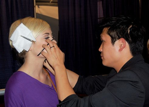 Model Alexandra Bartee sits back as designer David Yoo carefully applies strips of black tape to her face. The look was created to enhance Yoo's black-and-white collection featured on the runway Saturday during Charleston Fashion Week.