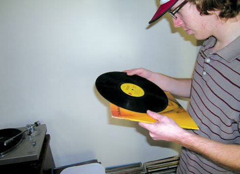 "Matt Douthit, 21, looks at his original copy of ""Goats Head Soup"" by the Rolling Stones, released in 1973. ""This is one of my favorites,"" he said."
