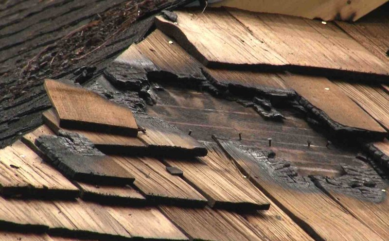 The charred wooden shingles next to the asphalt