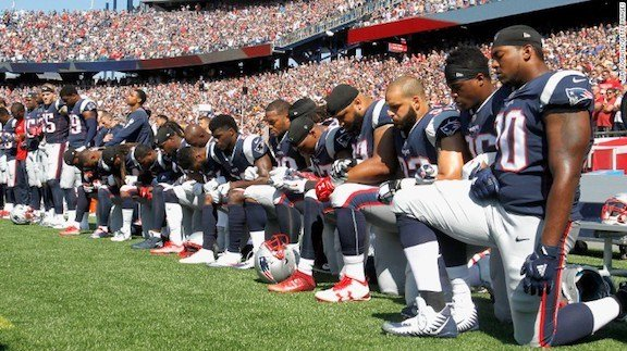 Image credit to CNN. Players from the New England Patriots taking a knee in protest during their game against the Houston Texans.
