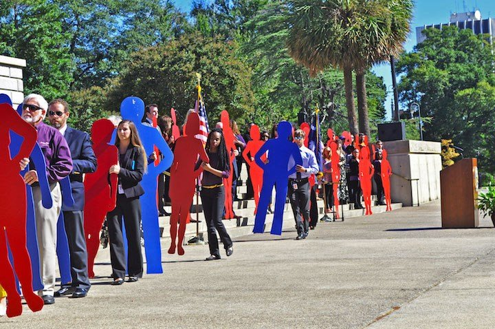 Volunteers and family members of the abuse victims carry red and blue cardboard slihouttes for the men and women who were murdered in 2016 by a family member of their household.