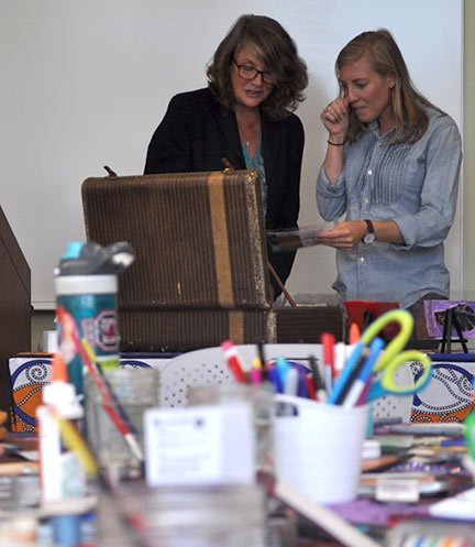 Caroline Lovell watches as Kelsey Phillips places her competed postcard in the traveling suitcase.