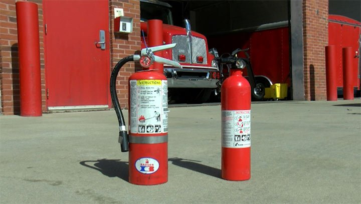 The fire extinguisher on the right is one of the recalled models, while the one on the left is an example of one with a metal head.