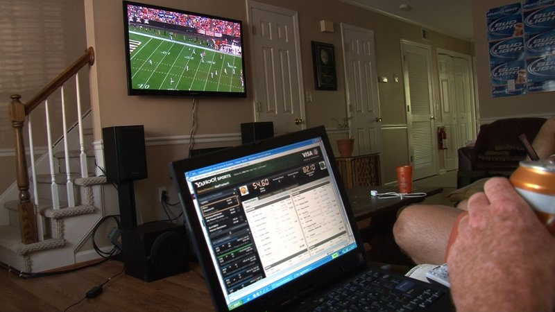 Fantasy Football owners watch the NFL games with their laptops to keep track of their players and their points.