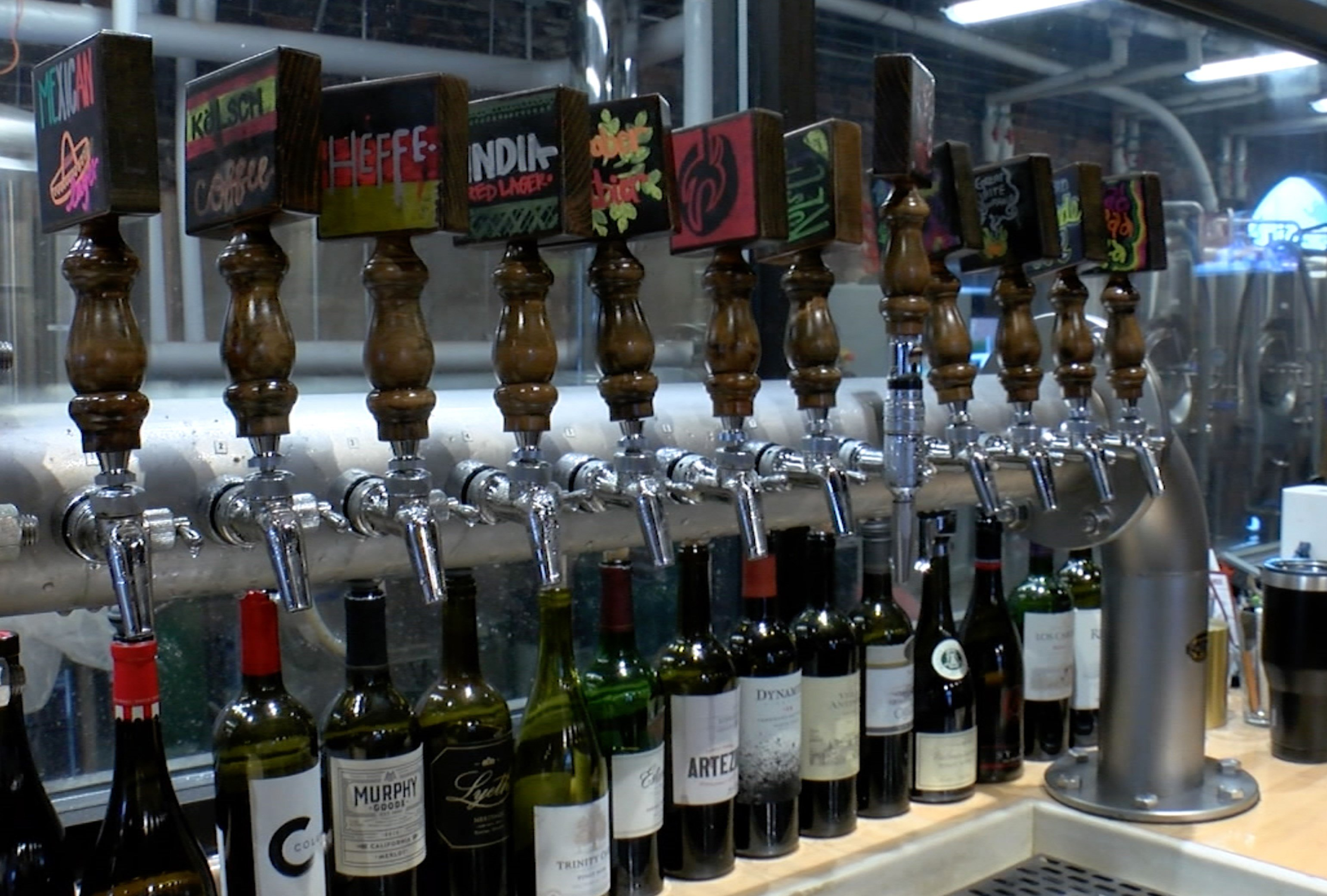 Some of the local beers available at Twisted Spur Brewery are displayed on the brew line.