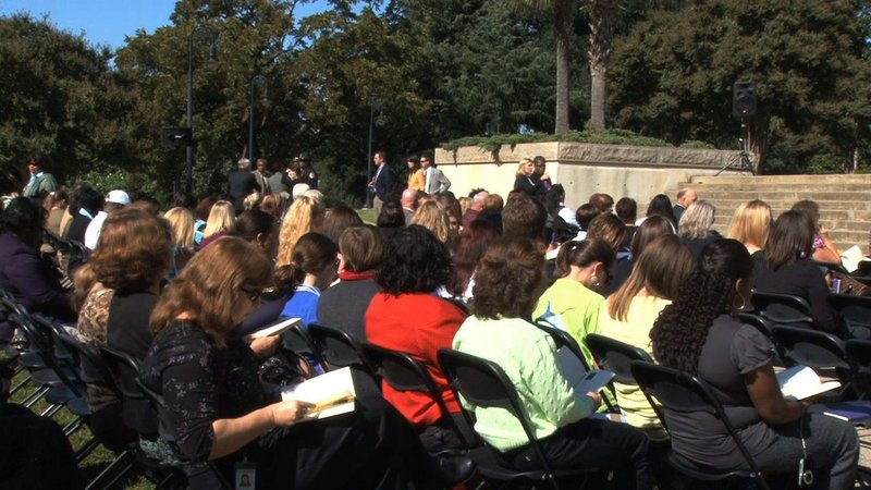 Onlookers gather at the State House to remember South Carolina's 2010 victims of domestic violence.