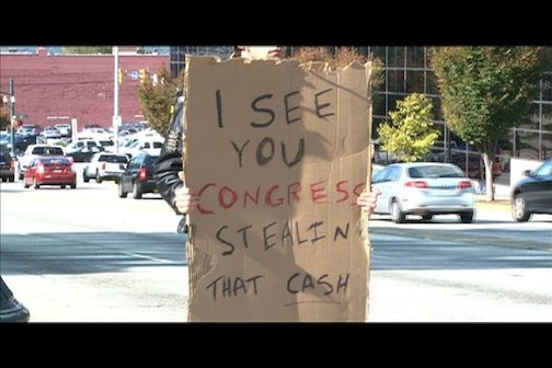 """Protesters are still carrying signs like """"I see Congress stealing that cash"""" to make themselves heard."""