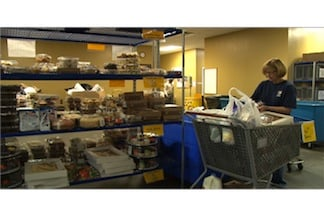 Harvest Hope volunteer stocks racks for needy families.