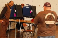 A poll worker prepares a machine for a voter at Sanders Middle School