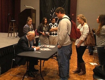 The founder of ESPN, Bill Rasmussen, signs autographs for USC students Wednesday night.