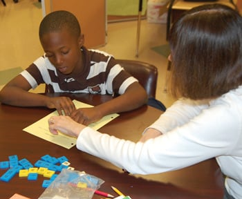 Third-grader Nicklas Entzminger receives help from Yvonee Jones, another tutor the Elys have recruited to help children after school at Hyatt Elementary School.