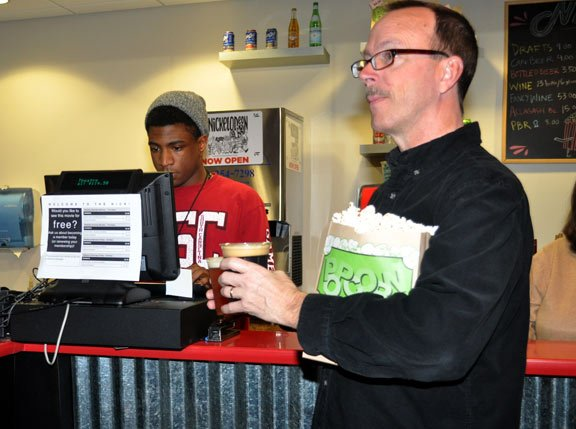 "Mike Switzer buys refreshments from employee Torres Perkins before watching ""Inside Llewyn Davis."""
