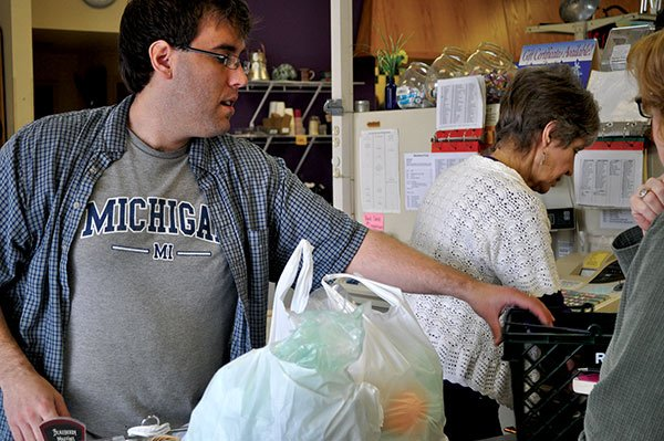 Nathan Tauog works along side fellow cashier Rowena Nylund at the Rosewood Market. Tauog, who has worked at the store for nearly seven years, said he's excited about the possibility of an increase in the minimum wage. Photo by Caitlyn McGuire.
