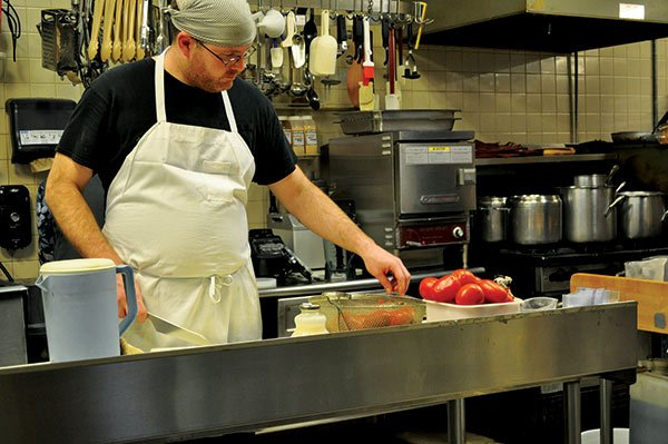 Rosewood Market employee Jim Mcfadden works behind the deli counter making sandwiches and desserts. He said although he makes above minimum wage, he is glad to see a potential increase for other employees. Photo by Caitlyn McGuire.
