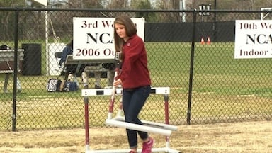 Captain Penny Boswell helps move hurdles onto the track.