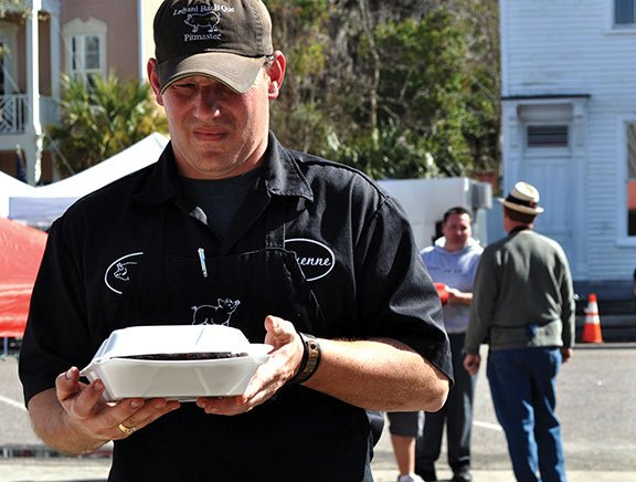 Competitition cook Cheyenne Ledyard of Ledyard Bar B Que Company brings his team's box of ribs to the receiving table at the Bands, Brews & BBQ competition. Ledyard BarBQue came in 18th place in ribs judging and 12th for butts.