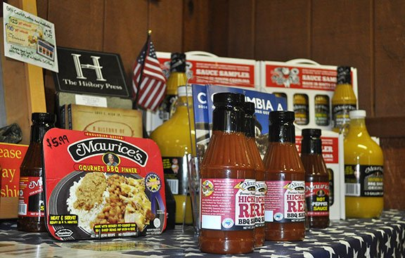"A collection of sauces and collectibles fill a table at Maurice's Gourmet Barbecue headquarters in Cayce. The restaurants are widely known for their famous ""Southern Gold"" sauce. Photo by Kyle Heck."