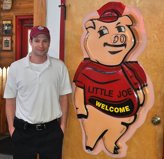 Paul Bessinger Jr. stands beside the pig that welcomes customers into Maurice's Barbecue in Irmo. Maurice Bessinger, founder of Maurice's and grandfather to Paul Jr., passed away Saturday after a battle with Alzheimer's. Photo by Kyle Heck.