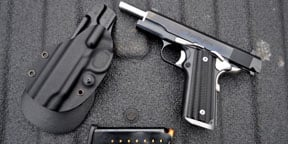The holster that carries Watson's M1911 pistol is designed to conceal the weapon on his hip.