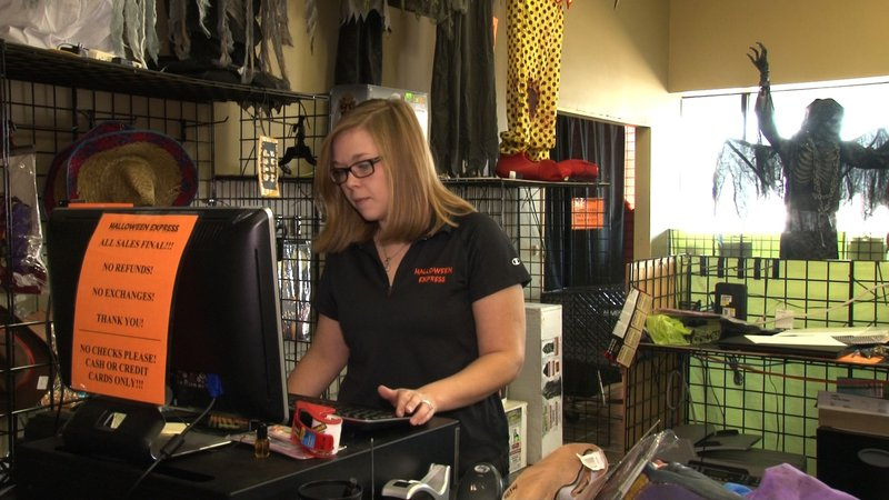 Store Manager Mitzi Creel rings up customers as they make their final purchases before Halloween.