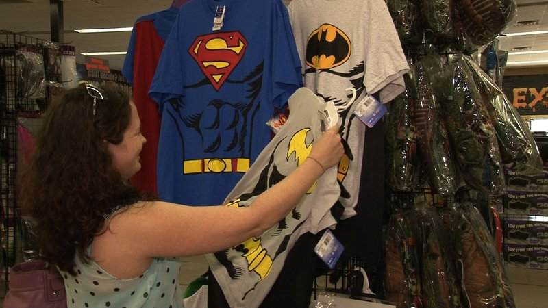 Christian Freeman looks through superhero costumes at Halloween Express.