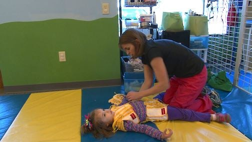 Physical therapist, Mandi Stoner, puts Sophie Zimmerman in the TheraSuit to begin her therapy session.