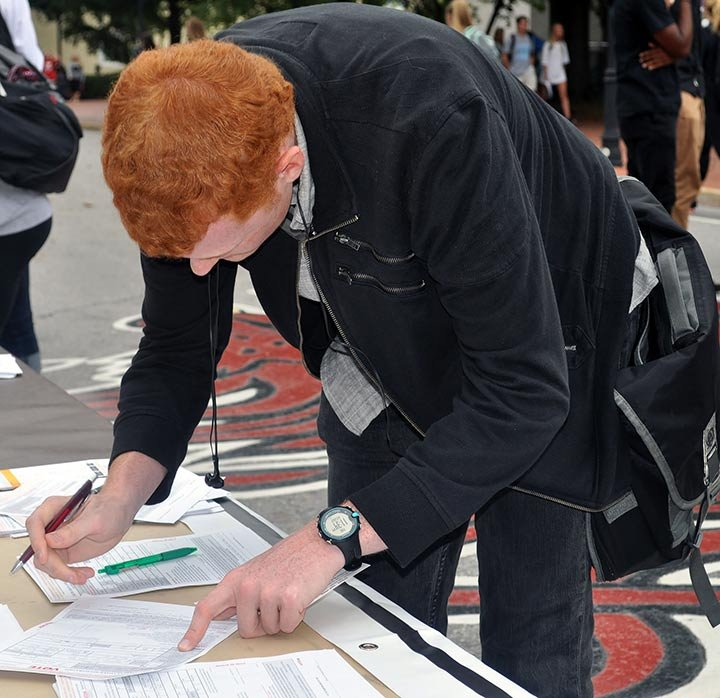 """Freshman Evan Dodge registers to vote for the first time at the University of South Carolina's voter registration day event. Dodge said everyone needs to vote because it's their """"civic duty."""""""